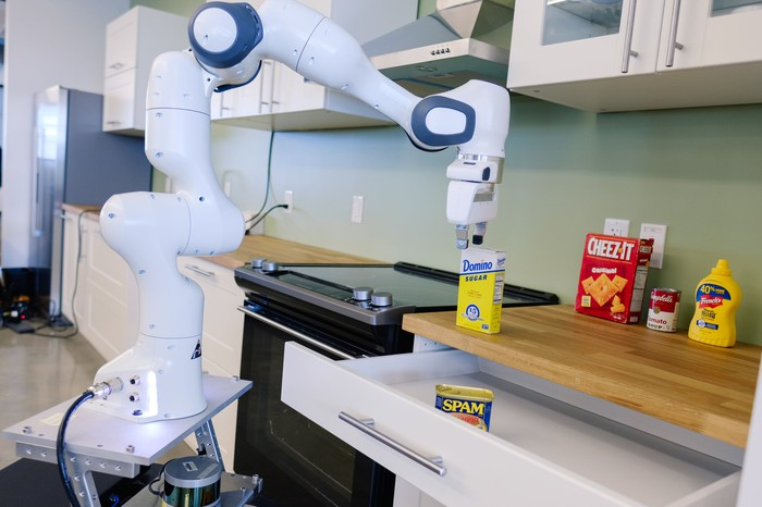 Robot arm working with food items in a kitchen.