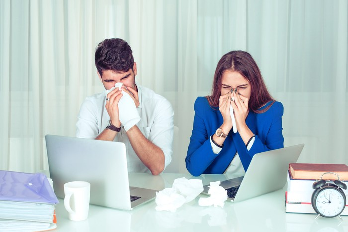 Man and woman at laptops blowing their noses into tissues.