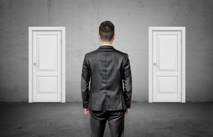 A businessman with his back turned stands between two identical closed white doors.