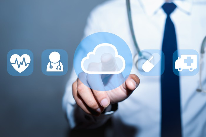 Man with a stethoscope around his neck pointing to a cloud icon next to healthcare icons