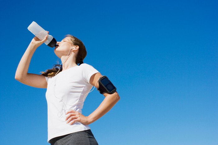 Woman dressed in athletic wear drinking from a water bottle with blue sky in background.
