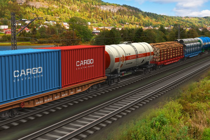 Freight train with assorted cargo rolling on tracks against a backdrop of greenery and houses.