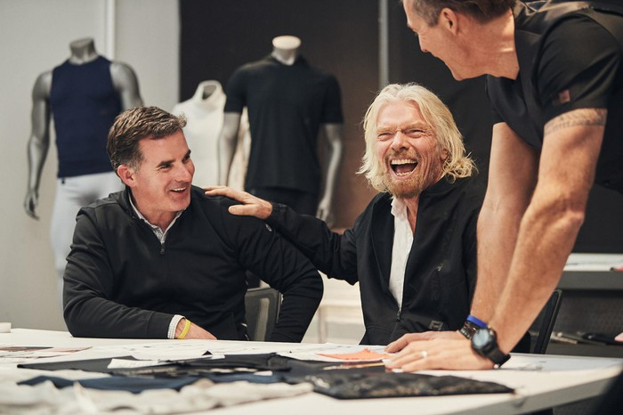 Under Armour CEO Kevin Plank and Virgin's Richard Branson are sitting at a table.