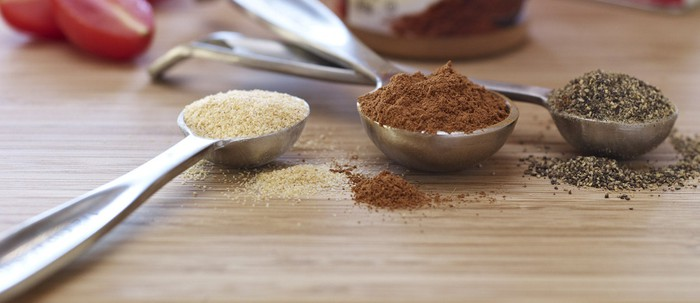 A selection of different spices in teaspoons.