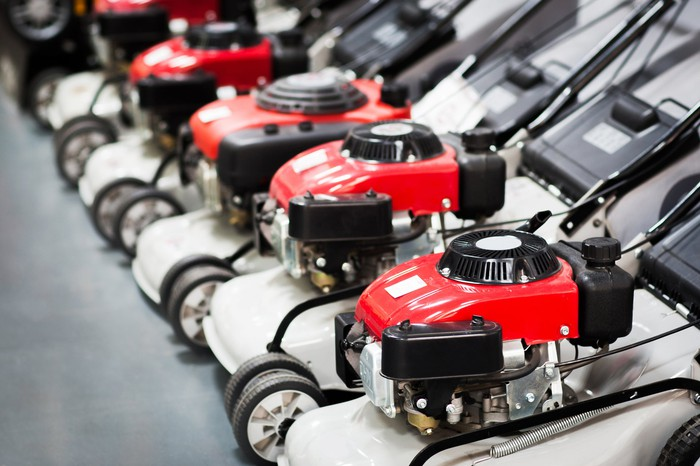 A row of shiny new lawn mowers lined up in a hardware store