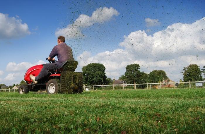 Man on riding lawn mower.