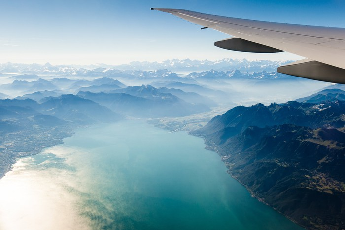 Airplane wing with aerial view of a valley.