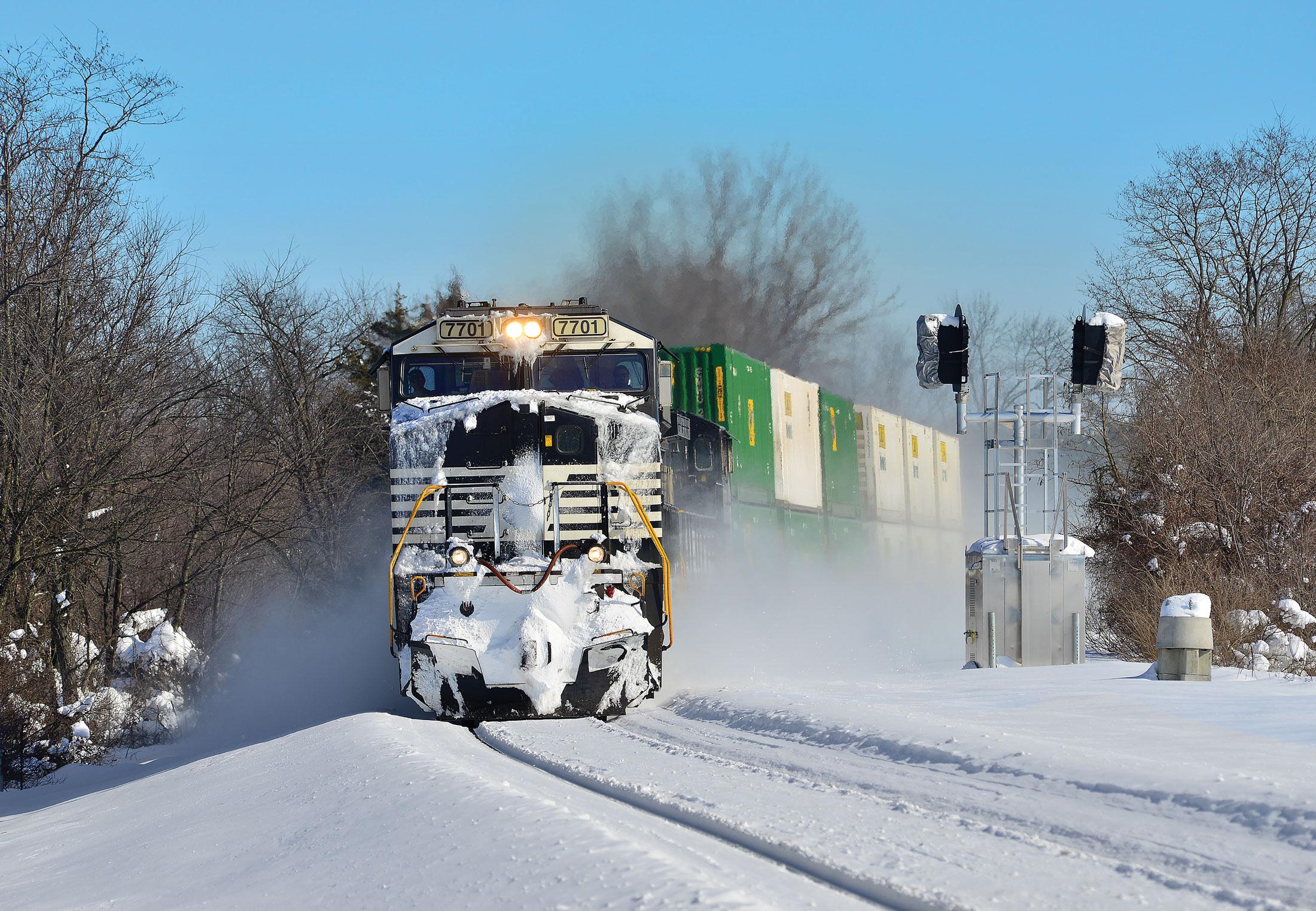 Locomotive pushing through snow.