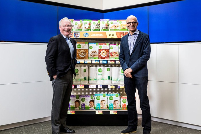 Kroger CEO Rodney McMullen (left) and Microsoft CEO Satya Nadella (right) standing in front of a grocery shelf.