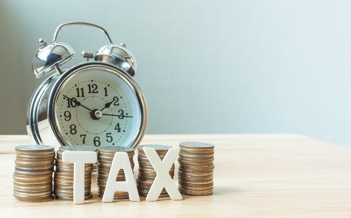 """Alarm clock, piles of coins, and letter magnets spelling """"TAX"""" on a wood table."""