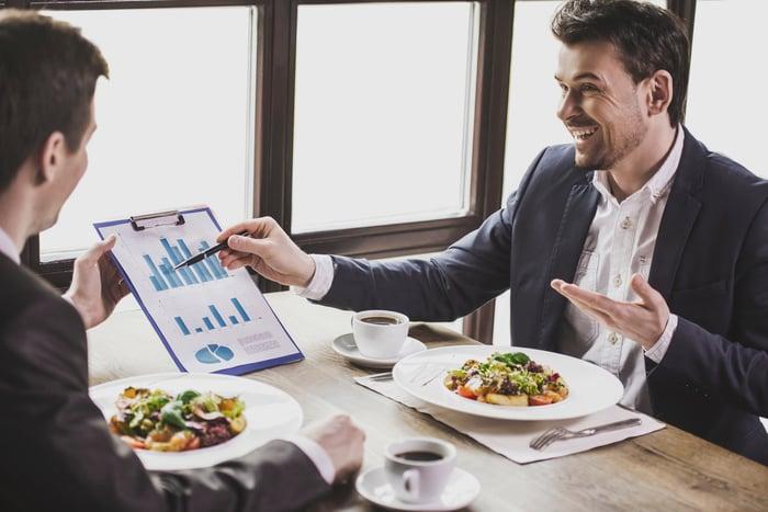 Men eating, conversing, and looking at charts.