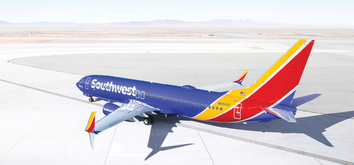 Airplane on tarmac in a desert environment, with Southwest colors and logo on it.