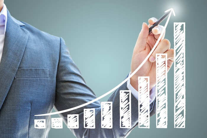 A businessman pointing to a growth trend on a bar chart