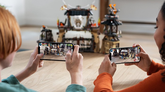 Two people viewing a toy castle through their iPhones.