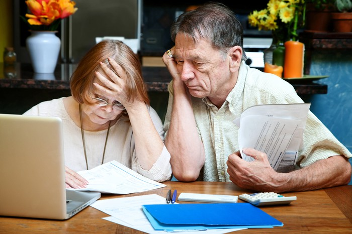 Senior couple looking at documents with concerned expressions