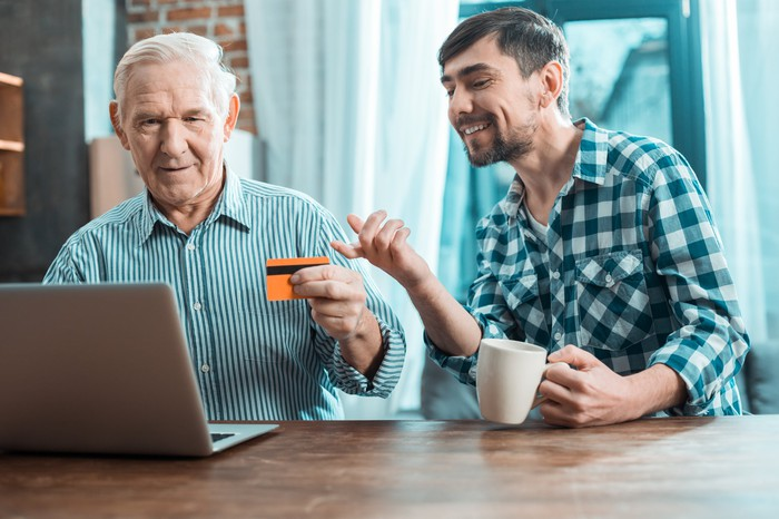 Older man at laptop holding credit card next to younger man with mug.
