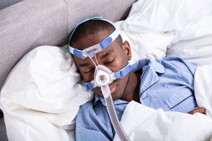 Man sleeping in bed with CPAP machine on his face