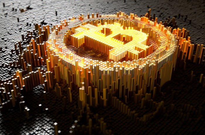 3-D mosaic of bitcoin symbol in gold surrounded by dark-grey mosaic bars.