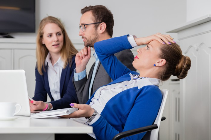 Woman sitting at her desk looking stressed