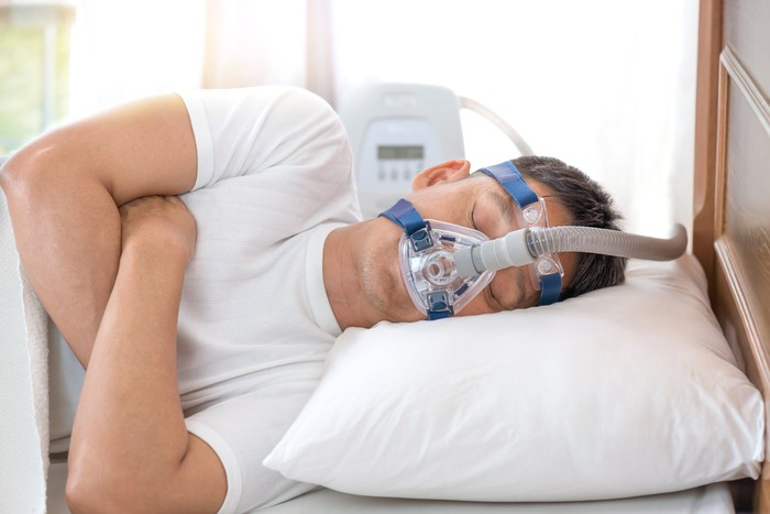 Sleeping man wearing CPAP mask.