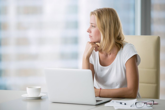 Woman with serious expression at laptop.