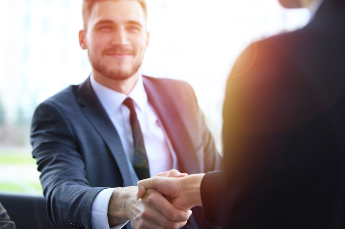 Man in suit and tie shaking hands with another person