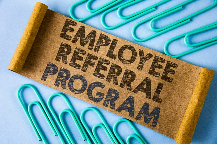 Piece of cardboard with employee referral program written on it on a blue background, surrounded by green paper clips