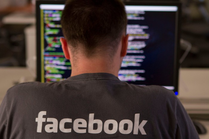 The back of a young man wearing a Facebook shirt working at a computer screen filled with code.