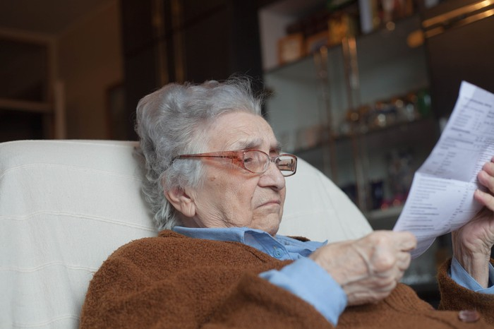 A bespectacled senior woman looking closely at a document while sitting on a chair