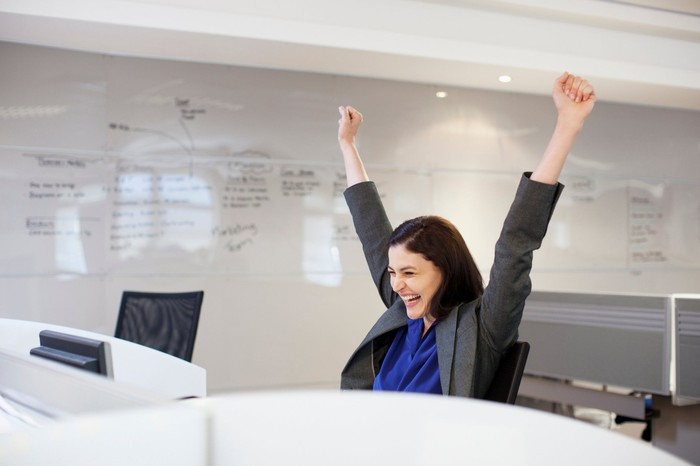 A woman in a suit throws her hands in the air in victory looking at her computer in an office.