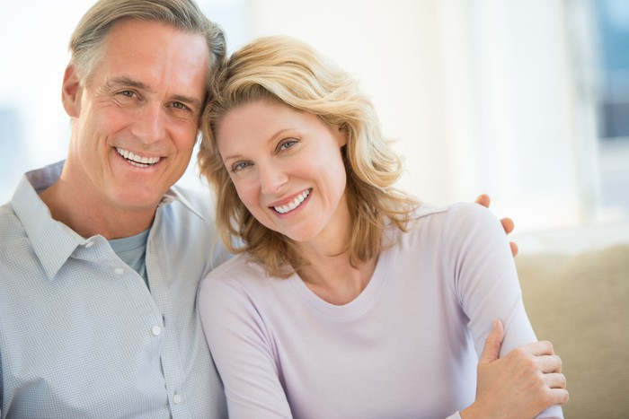 Smiling middle-aged couple sitting on a beige couch.
