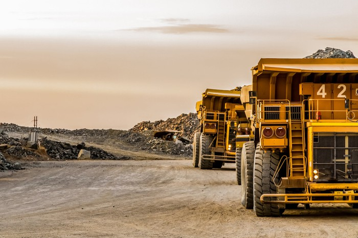Mining trucks standing next to a mine.