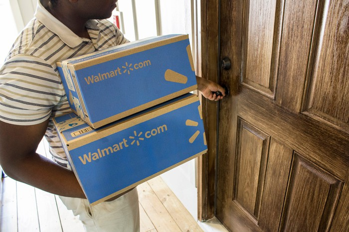 A person holding two boxes from Walmart.com while opening a door.