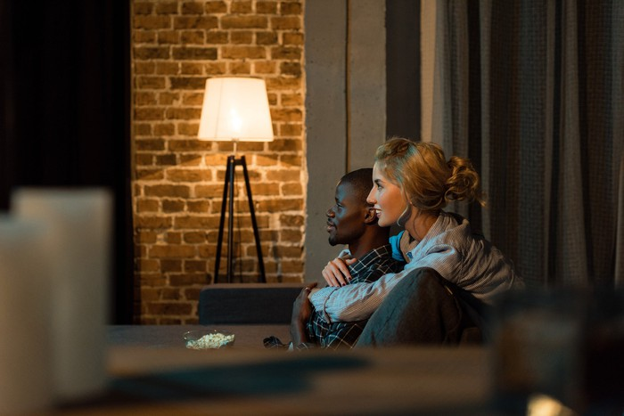 A couple sitting on a couch, watching TV, with a brick wall and light in the background.