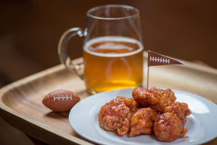 Wings and beer are next to a tiny football.