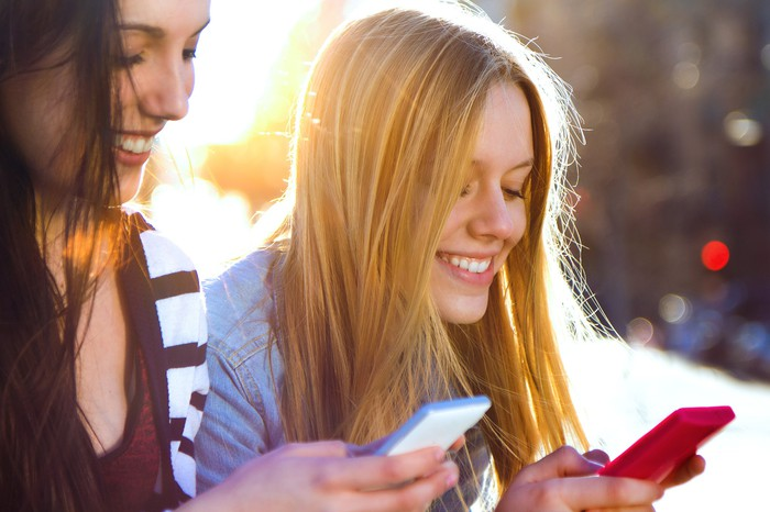 Two young women smiling as they text on their smartphones.