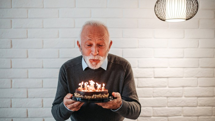 Man holding a small round cake and blowing out the lights