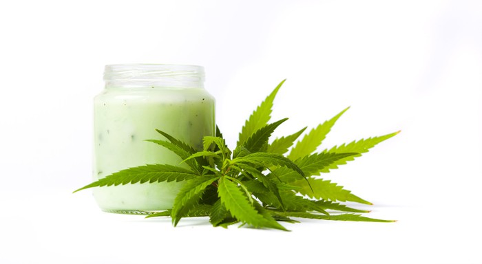 A jar of lotion next to cannabis leaves.