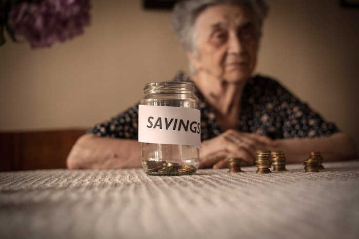 "Elderly woman with near-empty jar marked ""SAVINGS"" sitting in front of her on the table"