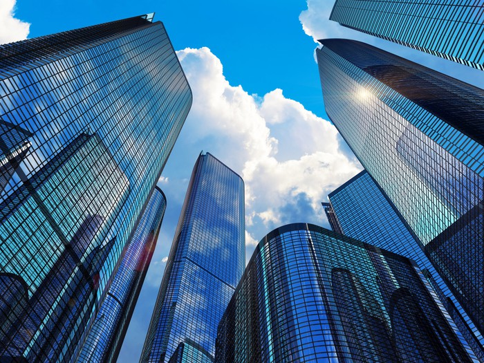 A group of office buildings pointing up to a cloudy blue sky.