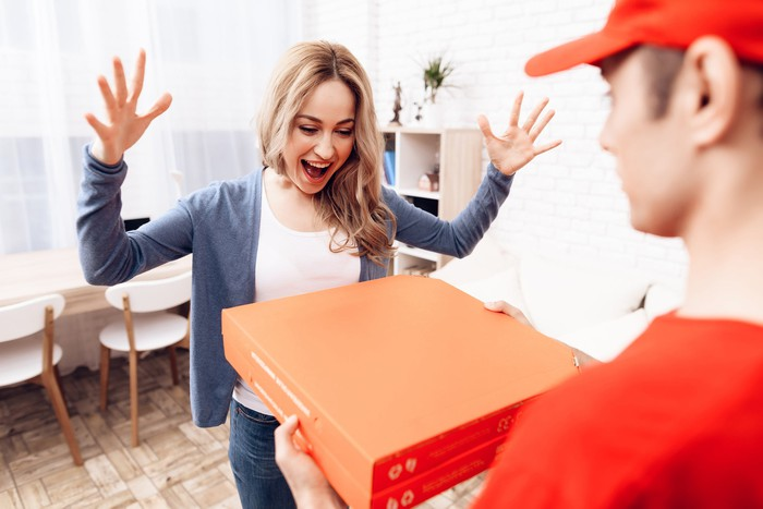 Man delivering pizzas to woman
