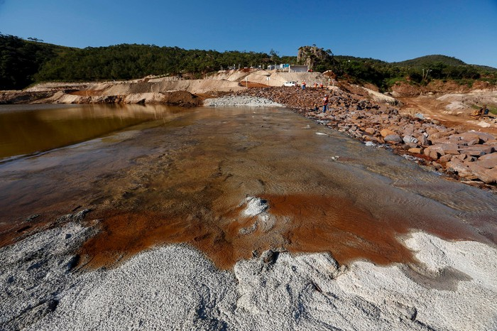 Tailings pond with brown water atop gray sand, with workers nearby.