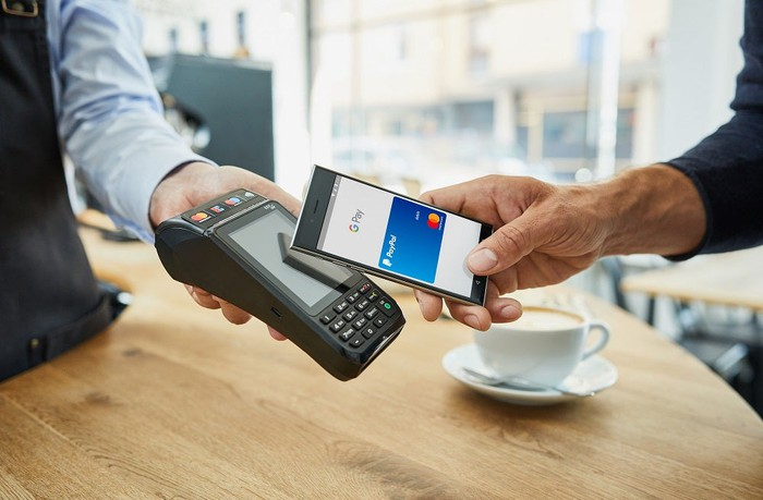 Shopper uses smartphone to make payment with a Mastercard.