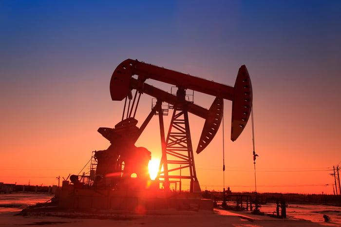 The sun setting behind an oil pump.