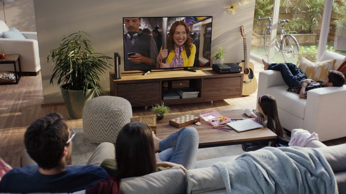 A man, woman, girl, and boy watching television in a living room