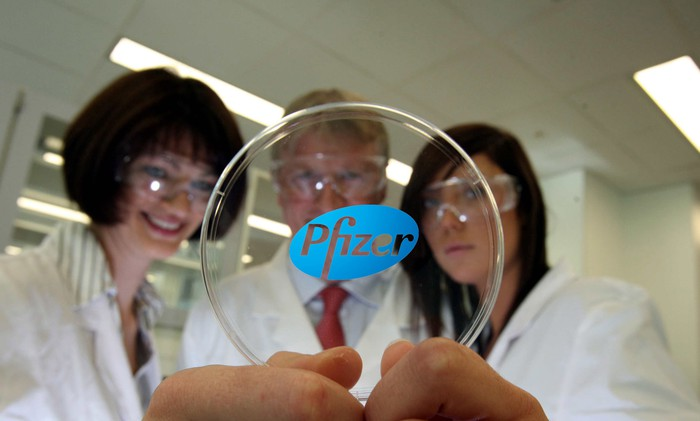 Three people wearing lab coats looking at a round piece of plastic with the Pfizer logo on it