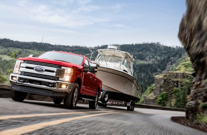 A red Ford F250 Lariat, a heavy-duty full-size pickup, towing a boat trailer up a mountain road.