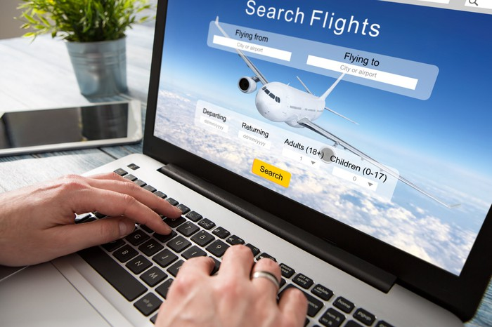 Man searching for flights on laptop.