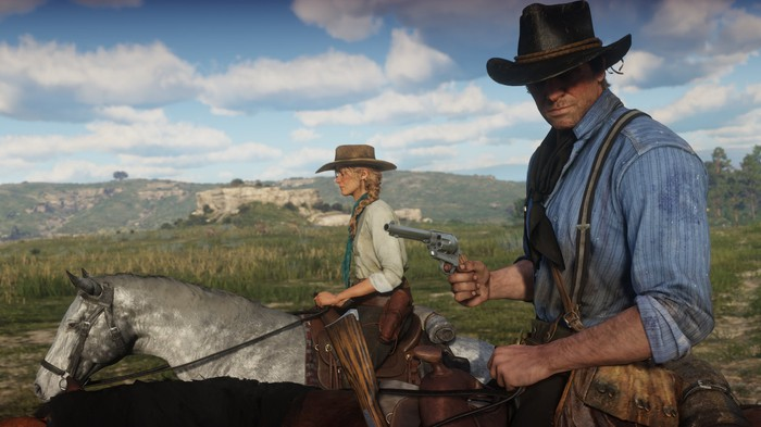A screenshot from Red Dead Redemption 2 with a man and a woman on horseback, with the man holding a pistol, his head cocked to the side as it listening.