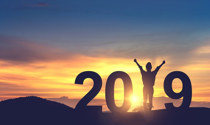 """Silhouette of a person on a hill making the 1 in """"2019"""" with sun in background."""